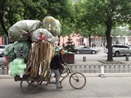 Another common CHinese contrast - guys carrying incomprehensible loads on bicycles whilst young yuppie types cruise by in huge 4x4s